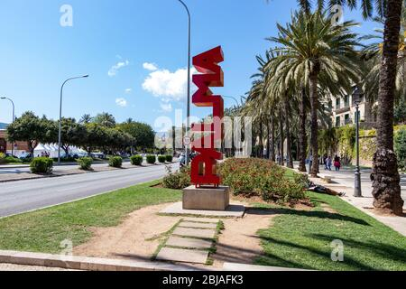 Palma, Mallorca, Spain - April 13, 2019: Big red Palma sign on roadside with palm trees in the background