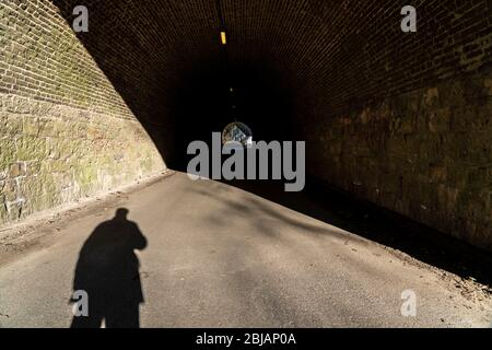 Shadow of a person, man, at the beginning of a tunnel, symbolic image, - Stock Photo