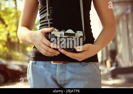 Woman with vintage camera, outdoors - Stock Photo