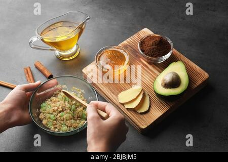 Female hands making nourishing facial mask with natural ingredients on grey background - Stock Photo