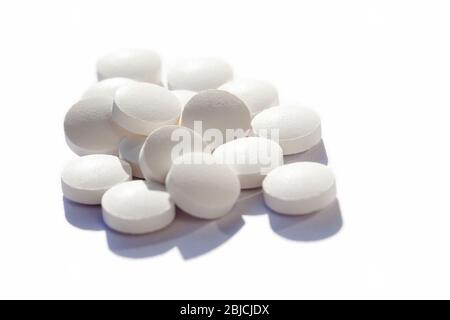 Many generic small round white pills, lots of little tablets on white background closeup. Simple group of little pills, medicine, medication and drugs - Stock Photo