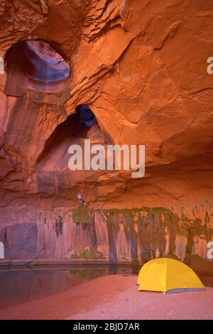 man rappelling into cave at Escalante's giant staircase
