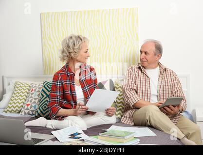 Senior couple calculating taxes at home - Stock Photo