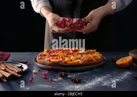 Woman chef decorating delicious tangerine pie on kitchen table - Stock Photo