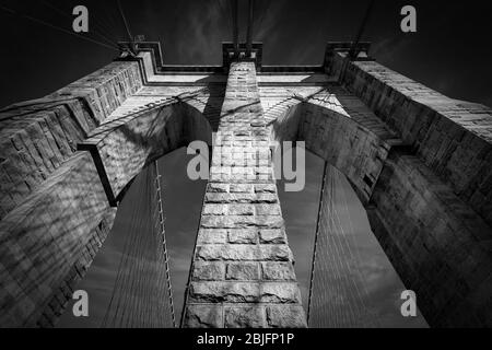 Looking up at one of the century old towers of the Brooklyn Bridge in New York City. - Stock Photo