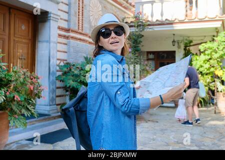 Tourism, woman visiting Christian monastery, female with map