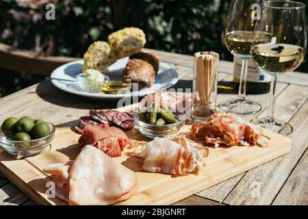 Two Glasses and Bottle of White Wine with Gourmet Charcuterie Board on round Marble Table. Garden Party. - Stock Photo
