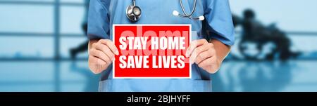 COVID-19 Social distancing quote medical nurse promoting staying at home to help workers. Coronavirus doctor holding sign in hospital background. Panoramic corona virus sign banner with text title. - Stock Photo