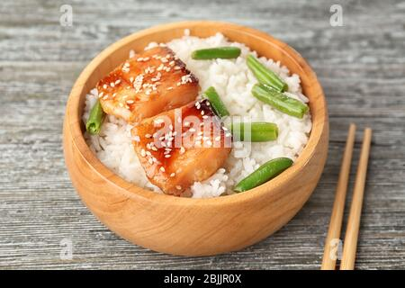 Fish fillet served with rice and green beans in wooden bowl on grey background - Stock Photo