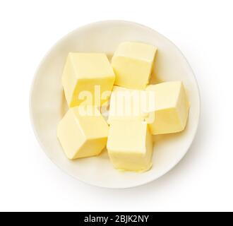 Butter pieces in white bowl isolated. Butter cubes. Top view. - Stock Photo