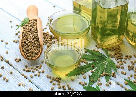 Composition with hemp oil in bowls on table - Stock Photo