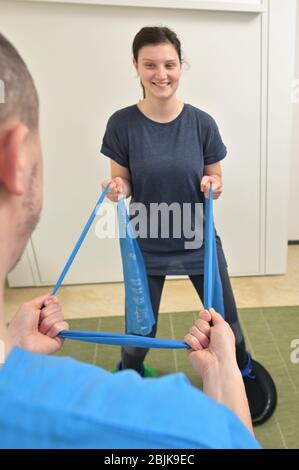 A young male physiotherapist helping a teen girl with stretching exercises.