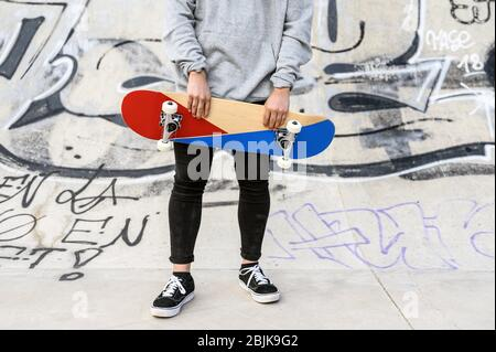 Close up of unrecognizable young man holding skateboard in the park.