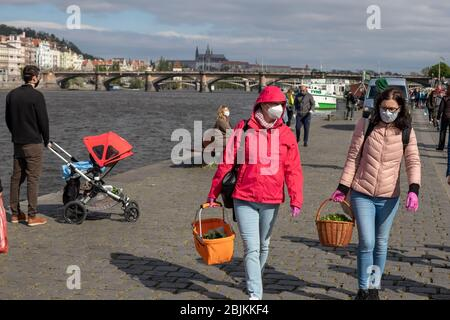 PRAGUE, CZECH REPUBLIC - APRIL 25, 2020: Women wearing protective face masks and gloves at the Naplavka farmers market, re-opened for the first time s - Stock Photo