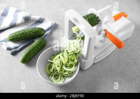 Spiral vegetable slicer with cucumber spaghetti on table - Stock Photo