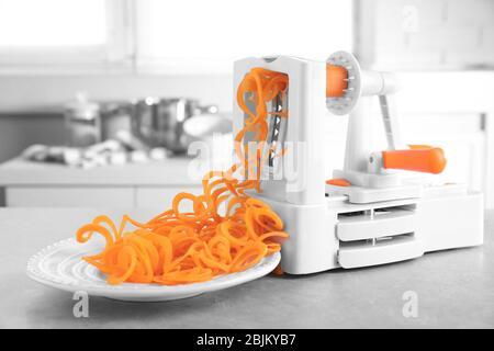 Spiral vegetable slicer with carrot spaghetti on table - Stock Photo