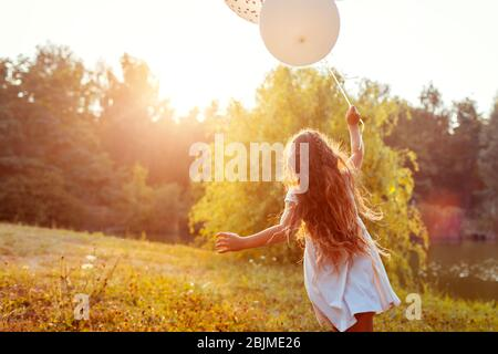 Pretty little girl running with baloons in hand. Kid having fun in summer park. Outdoors activities Stock Photo