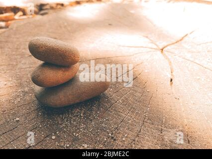Yoga Zen stones balance on top of each other. Sea pebbles lies on a wooden saw lit by the sun. Copy space.