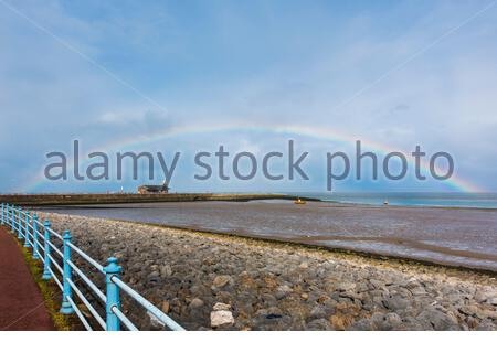 Morecambe, Lancashire, UK. 30th Apr, 2020. With April showers, a rainbow shines over the Stone Jetty on Morecambe Promenade. Changeable and cooler weather is forecast to continue going into the weekend with rain providing some relief to gardeners at the end of a very dry month. Credit: Keith Douglas News/Alamy Live News - Stock Photo