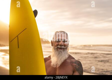 Happy fit senior having fun surfing at sunset time - Sporty bearded man training with surfboard on the beach Stock Photo