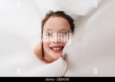 Portrait of a young girl wearing make-up wrapped in a curtain
