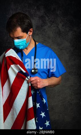 Sad/pensive male doctor in blue hospital scrubs with face mask and stethoscope, nursing the Stars & Stripes American flag close to his chest.