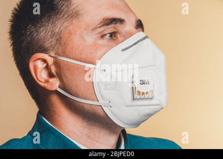 Wuhan, China - April 21 2020: Closeup of face male patient in medical mask 3m on self isolation during coronavirus pandemic 2021