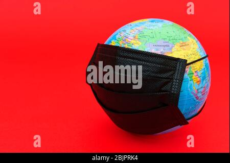 Earth globe model with black surgical mask isolated on red background. Concept: Quarantined earth. Protection against Coronavirus. - Stock Photo