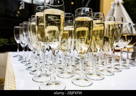 Glasses with champagne at a buffet at a wedding party. Secular reception, new year, wedding. Soft focus. Glasses with Proseko at the holiday. Many gla - Stock Photo