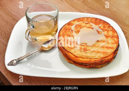 Waffle cake with a spoon lying smeared with condensed milk, a Cup of green tea - Stock Photo