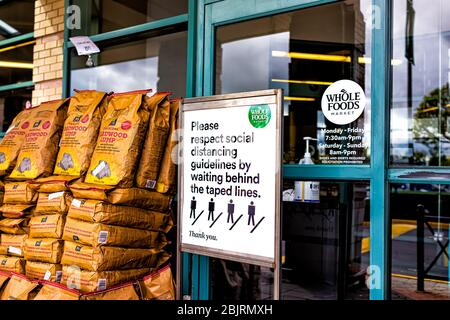 Reston, USA - April 27, 2020: Northern Virginia at Plaza America Whole Foods Amazon grocery store sign for social distancing at shop entrance - Stock Photo