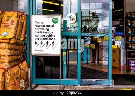 Reston, USA - April 27, 2020: Northern Virginia metro area Plaza America Whole Foods Amazon grocery store sign for social distancing at shop entrance - Stock Photo