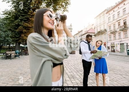 Young beautiful tourist woman exploring the city, making photos of famous places. African man and Caucasian girl holding city map and exploring new - Stock Photo