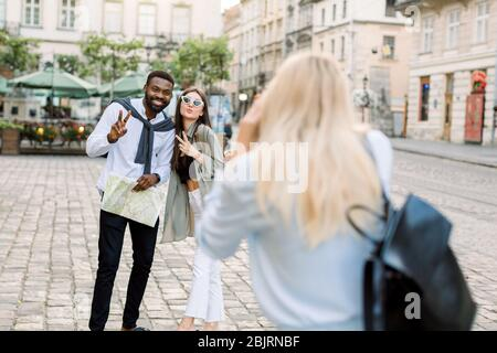 Excited cheerful mix raced couple, African man and Caucasian girl, enjoying walking outdoors, in the center of ancient European city, while their