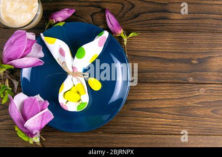 Small White Rabbit Figurine with White Easter Eggs and Pink Orchids and Blossoms on Rustic Wooden Background - Stock Photo
