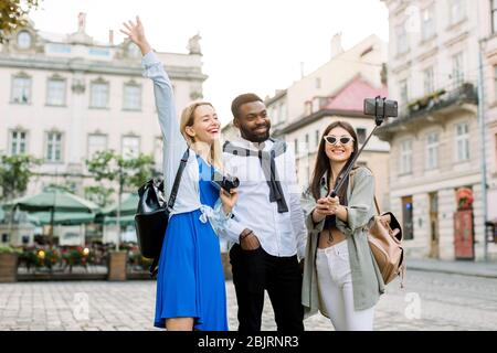 Excited cheerful mix raced friends enjoying walking outdoors in European city. Man and two women walking outside, hugging each other, laughing and
