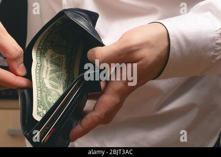 man shows a wallet with one dollar in a white shirt in the office - Stock Photo
