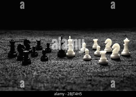 chess pieces confrontation two kings with their armies fighting on black concrete dark background .copy space - Stock Photo