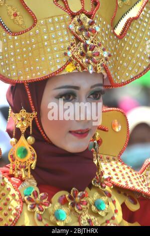 TARAKAN - INDONESIA, 25 July 2018 : Portrait of a beautiful Indonesian woman smiling wearing modified custom carnival clothes. APEKSI Cultural Parade Tarakan City in 2018