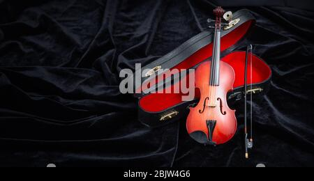 violin with a case on dark velvet with copy space