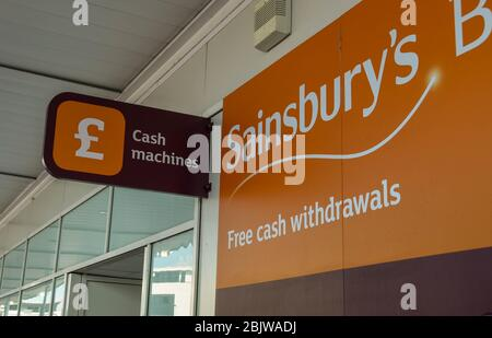 SWANSEA, WALES - JULY 2018: Exterior of a Sainsbury's supermarket in Swansea with a sign for a cash point machine - Stock Photo