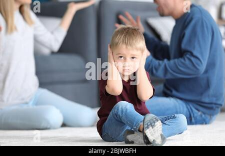Sad little boy in room with quarreling parents. Family conflict - Stock Photo