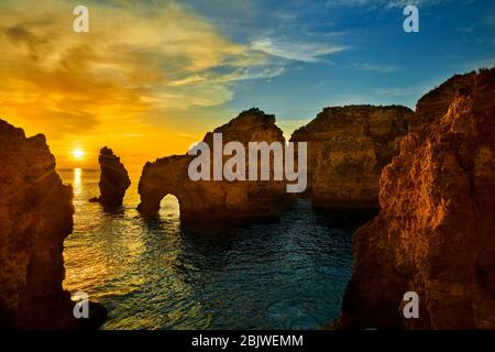 Sun rises among the rock formations along the southern coast of Portugal in the town of Lagos. - Stock Photo