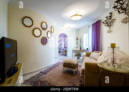 Large cozy bedroom in classic style, beige furniture, rugs and mirrors. - Stock Photo