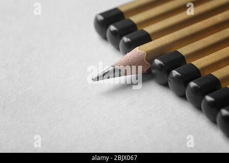 One pencil standing out from others on color background. Difference and uniqueness concept