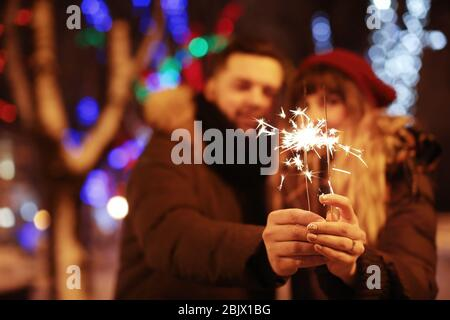Young loving couple holding sparklers outdoors on winter evening - Stock Photo