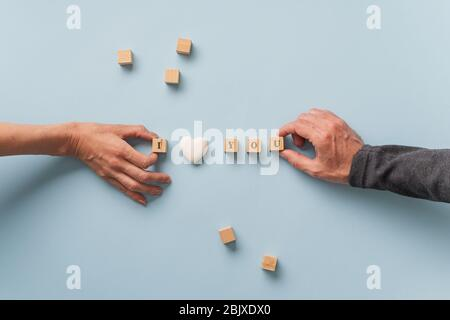Male and female hand making an I love you sign spelled on wooden blocks with heart shaped marble in the middle. - Stock Photo