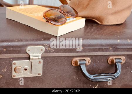 Vintage suitcase with sunglasses, book and hat. Ancient brown suitcase for journey.