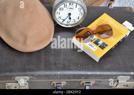 Vintage suitcase, book, sunglasses and hat. Suitcase ready for vacation.