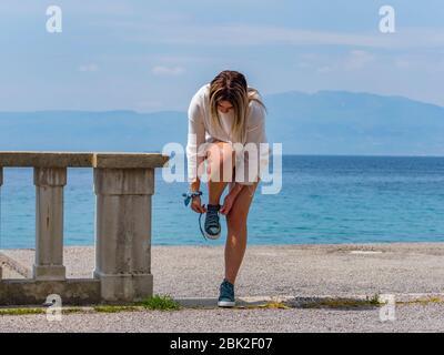 Teengirl tying laces on sneakers footware footwear by standing on one leg on seaside looking down - Stock Photo